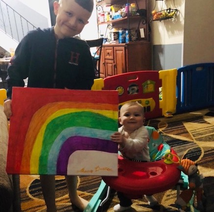 a baby in a walker helping her brother hold up his rainbow drawing