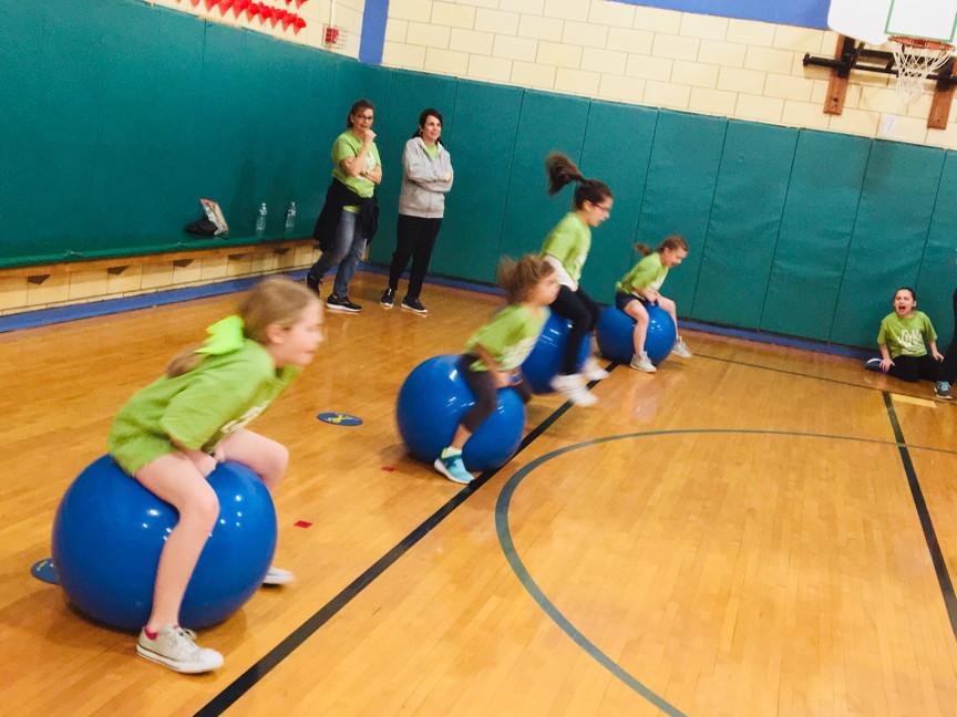 students sitting on big blue balls