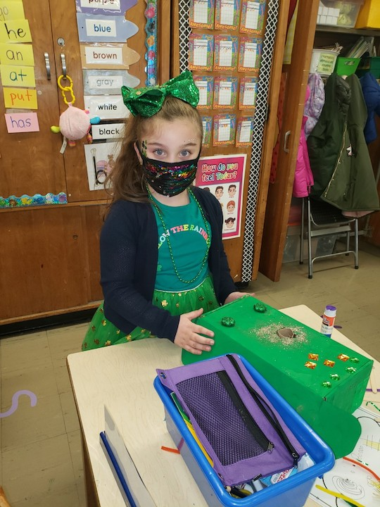 A child in green is decorating her box to catch a leprechaun