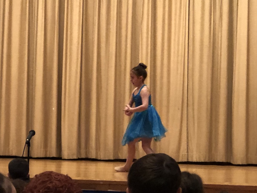 a girl in a blue tutu ready to dance