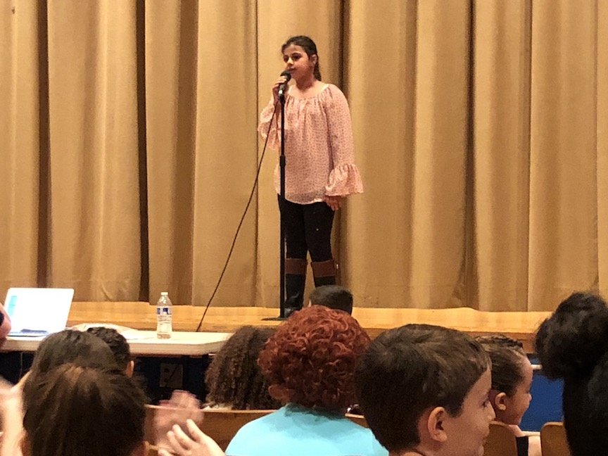 a girl in a pink top singing