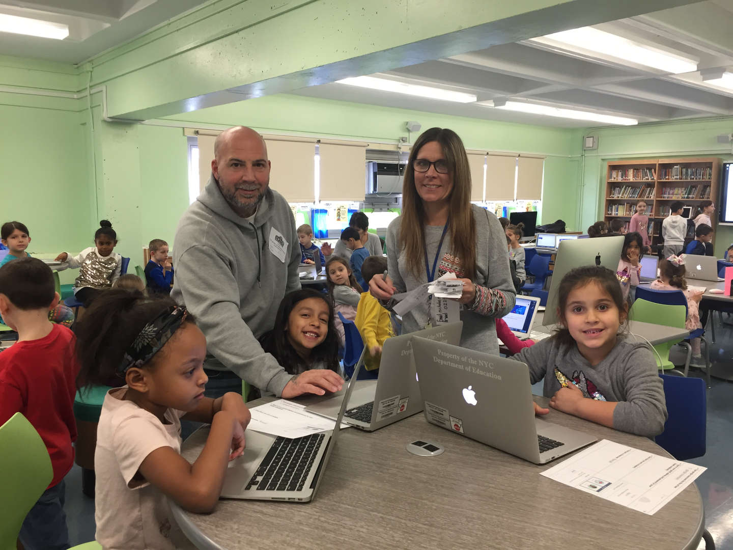 Teacher and parent helping the students in the media center