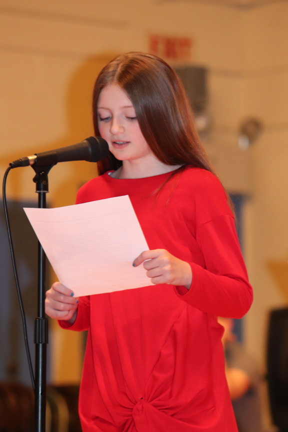 a girl reading from a paper