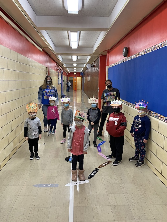 Pre K students in the hallway wearing their 100th day crowns!