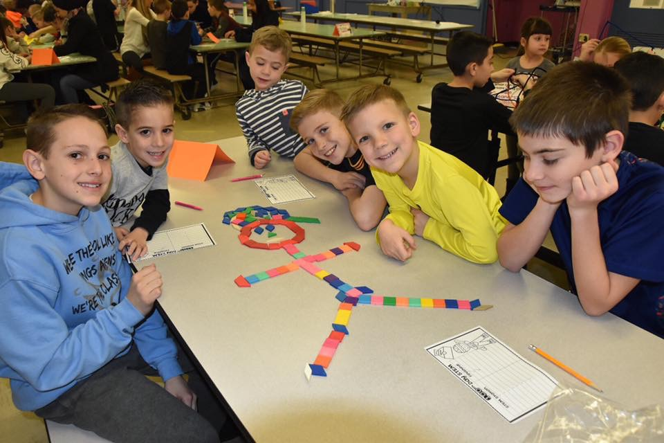 Students making pictures with 100 cubes