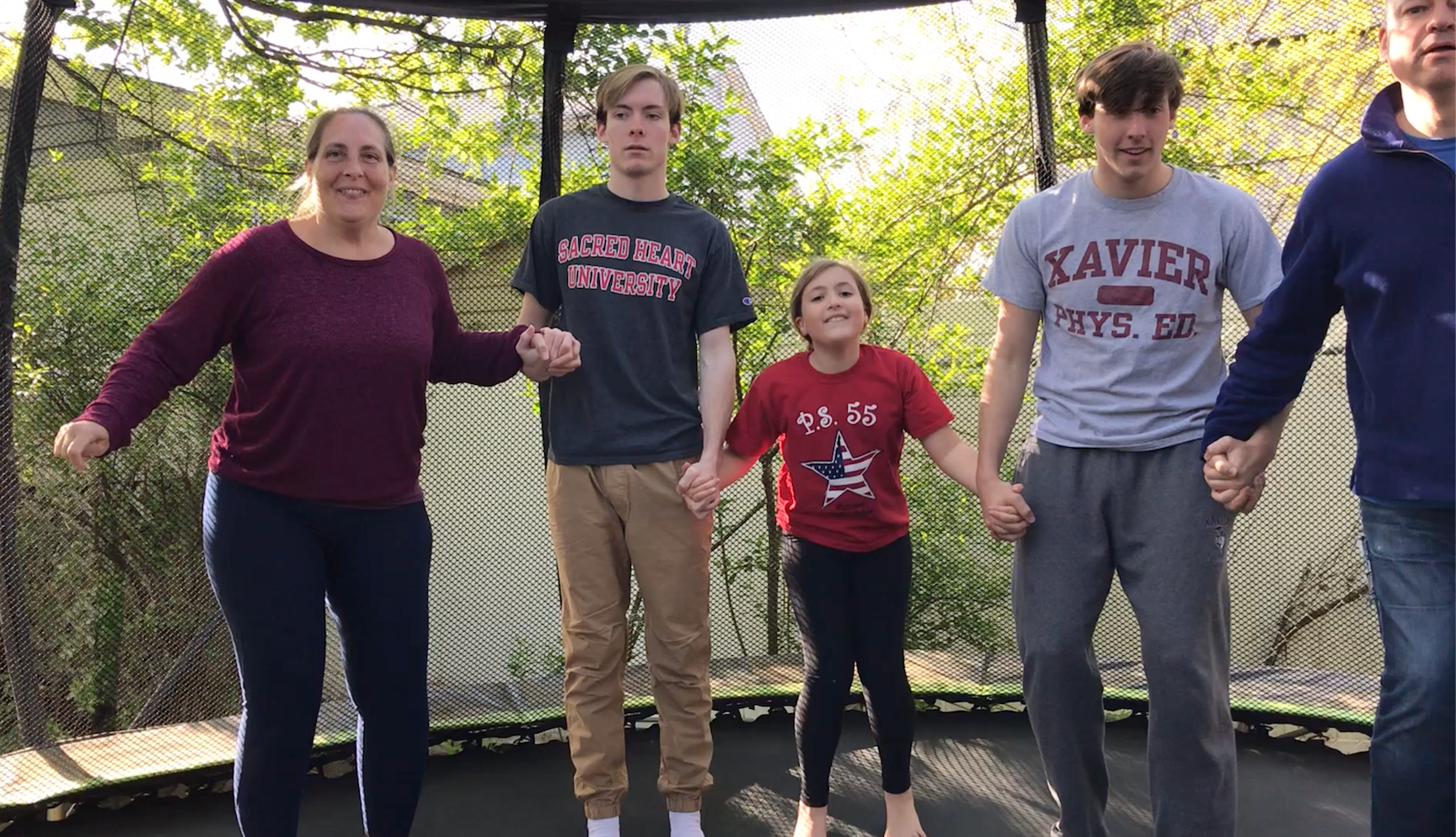 Here is a family of five jumping on their trampoline together and having fun!