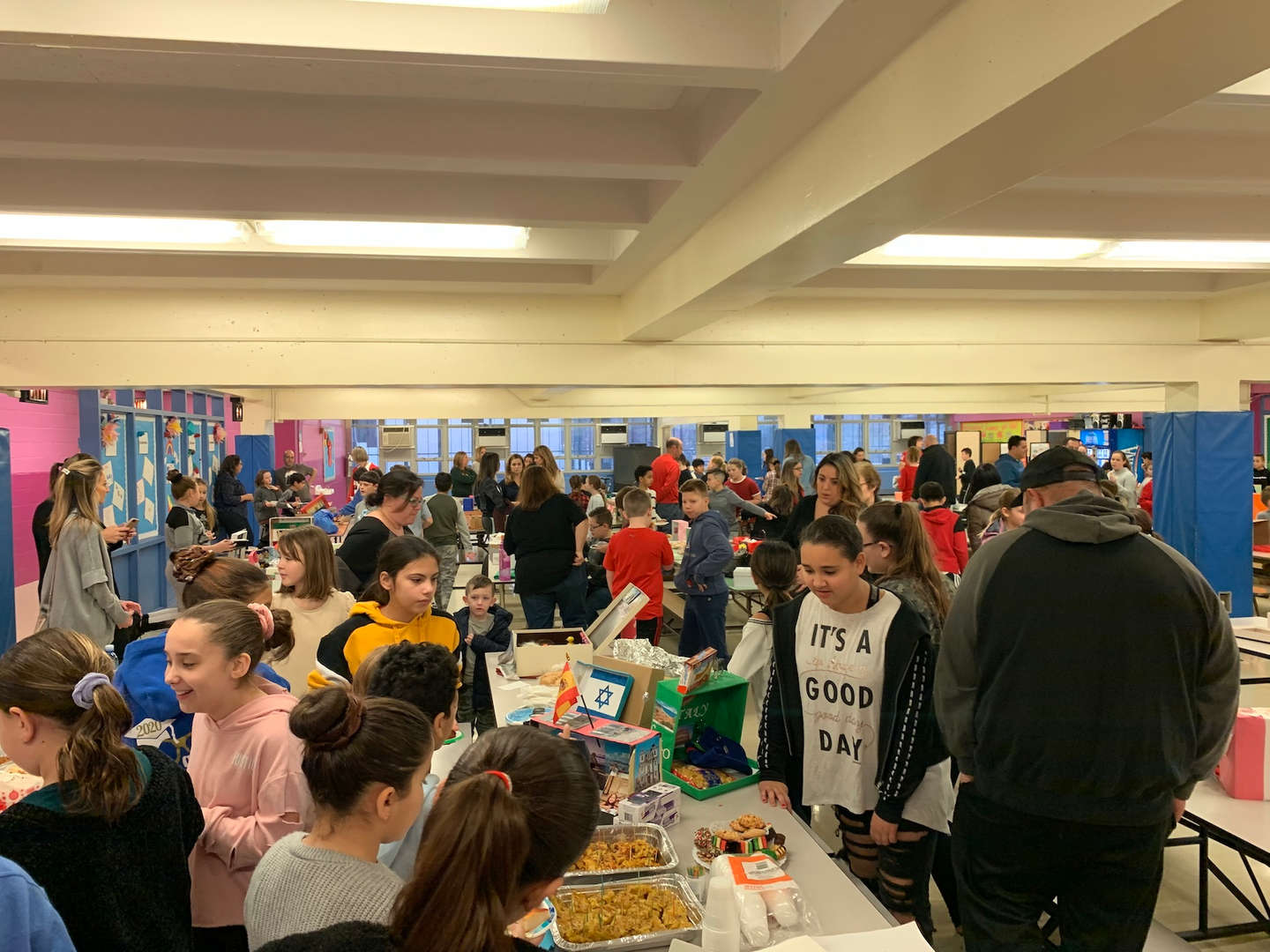 A view of the crowded room of people and food displays.