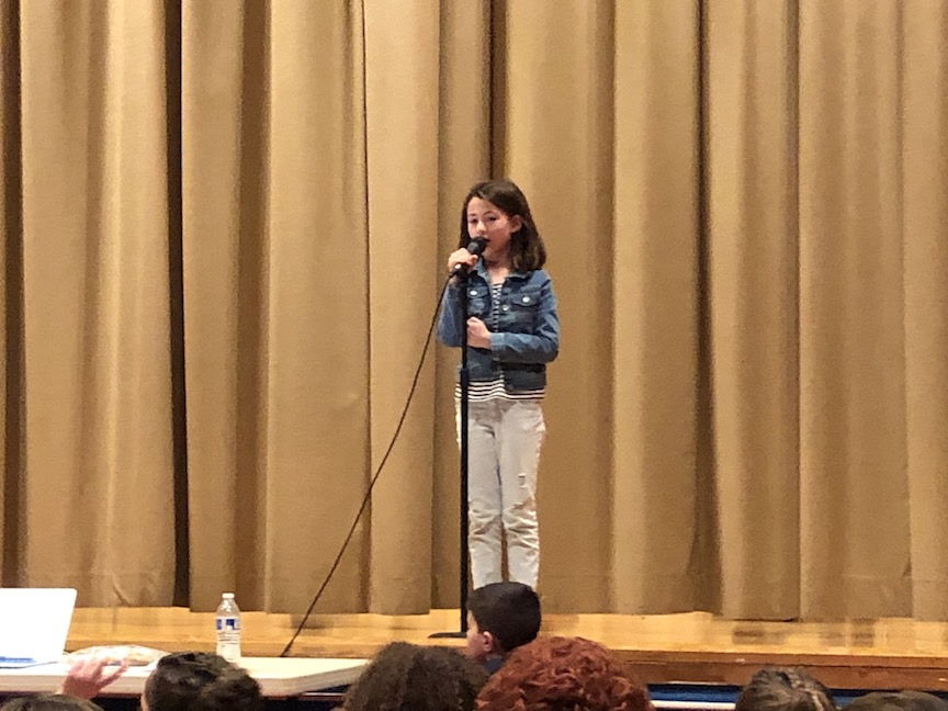 a girl in a blue jacket singing