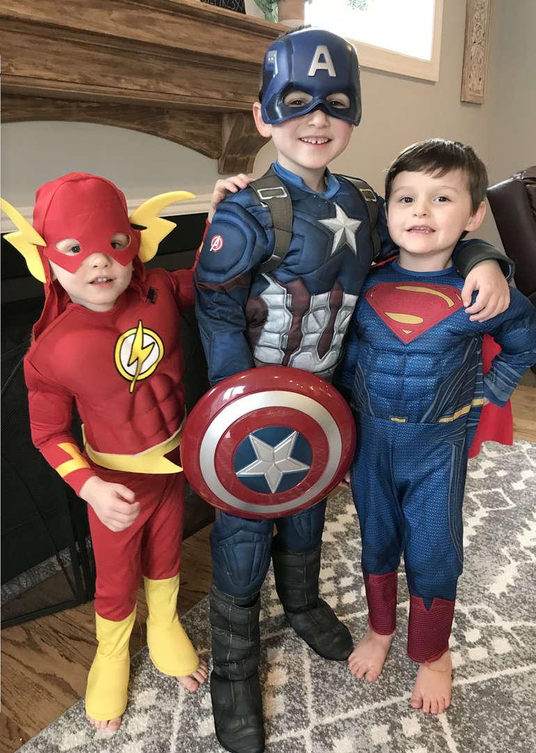 3 superheroes arm in arm