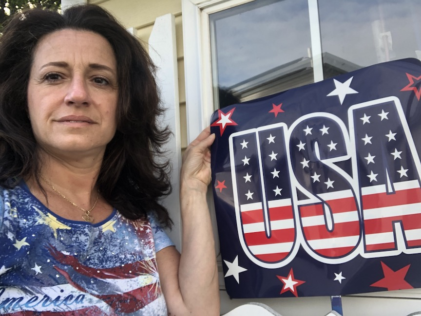 This patriotic teacher is wearing red, white and blue to match the sign she is holding up