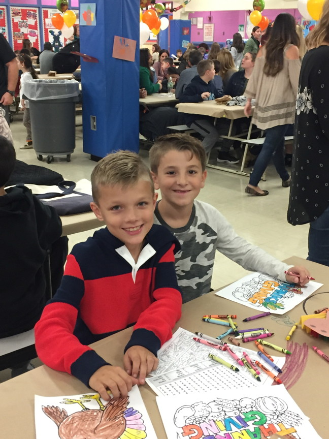 two boys smiling and coloring