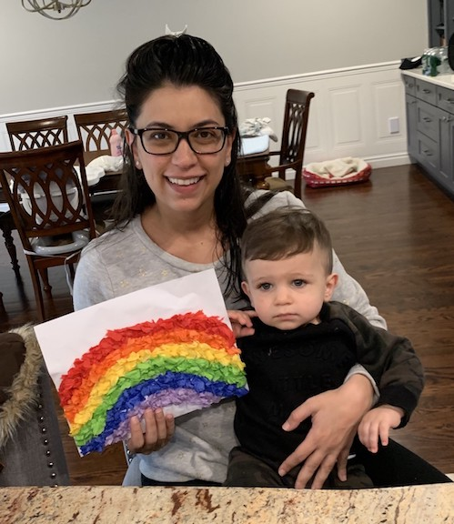 a mom is holding up a rainbow made using crepe paper and her baby