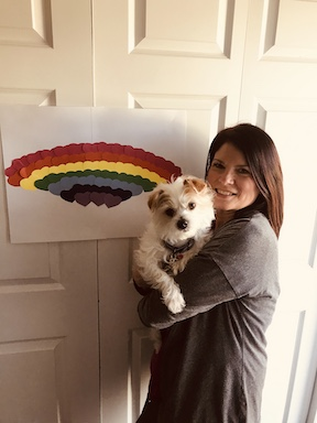 a teacher holding a dog is standing next to her rainbow hanging on a door
