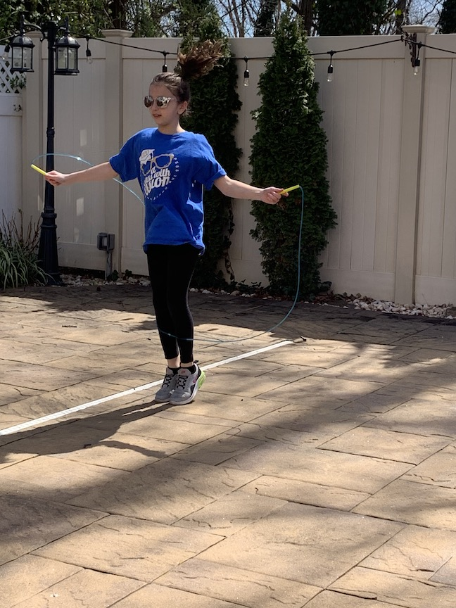 girl in a blue tee jumping in a yard