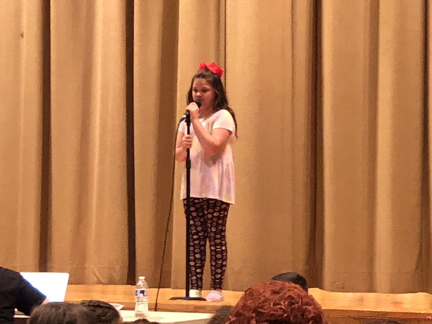 a girl with a red bow in her hair singing