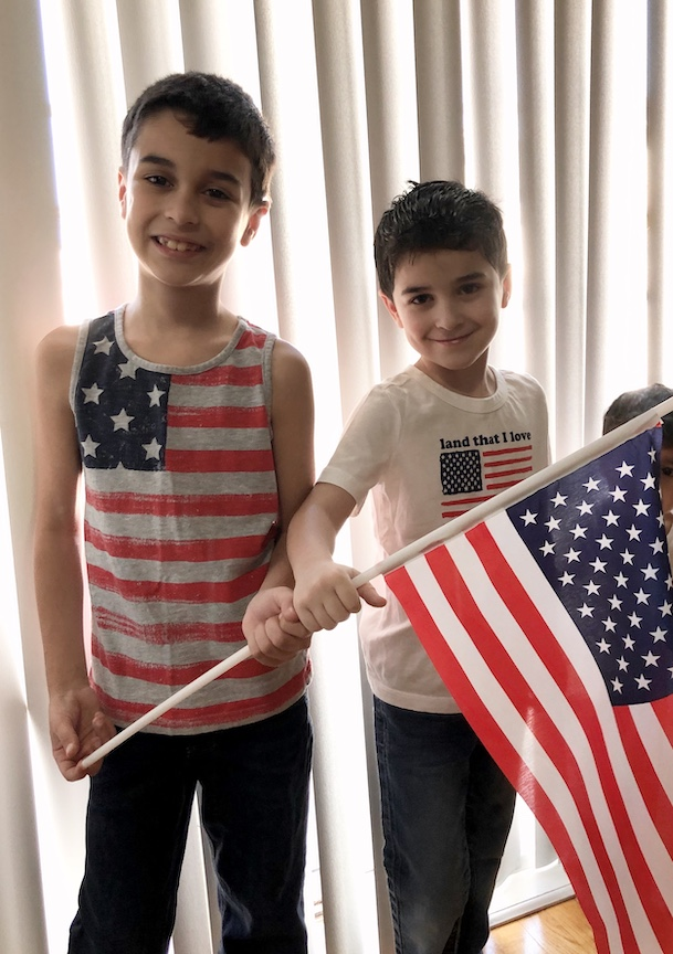 These two children are wearing the stars and stripes while holding up a flag