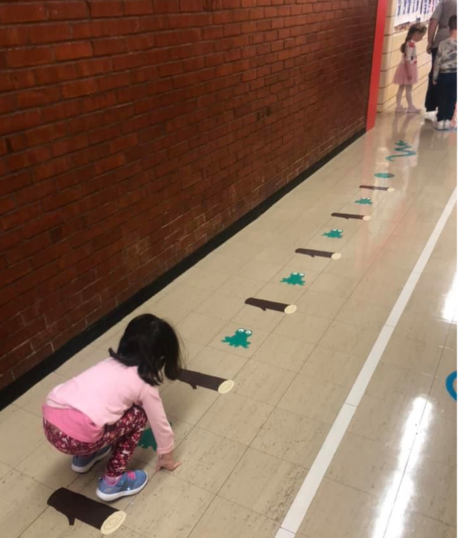 a girl is hopping down the hall following the frog picture trail